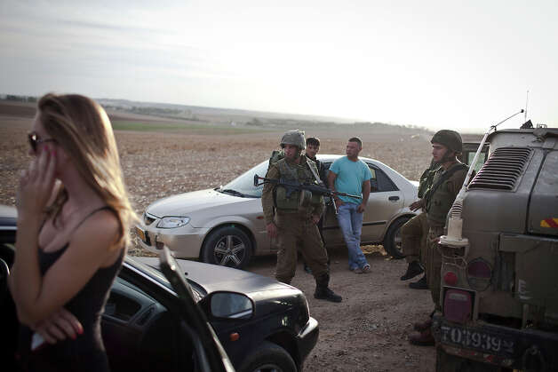 Israeli soldiers talk with civilians during a patrol next to the Israeli-Palestinian border as some 16,000 reserve troops are drafted in, on November 16, 2012 in Israel. Conflict between the Israeli military and Palestine militants has intensified over the last few days, with Israel striking some 130 targets overnight. According to reports, 18 Palestinians and three Israelis have been killed. Egypt's prime minister Hisham Qandil is due to make a brief visit to Gaza today and Israel have vowed to suspend fire for the duration of his visit, provided there's no cross border attacks from militants. Photo: Ilia Yefimovich, Getty Images / 2012 Getty Images