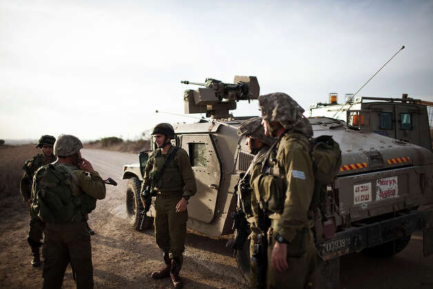 Israeli soldiers patrolling next to the Israeli-Palestinian border as some 16,000 reserve troops are drafted in, on November 16, 2012 in Israel.  Conflict between the Israeli military and Palestine militants has intensified over the last few days, with Israel striking some 130 targets overnight. According to reports, 18 Palestinians and three Israelis have been killed. Egypt's prime minister Hisham Qandil is due to make a brief visit to Gaza today and Israel have vowed to suspend fire for the duration of his visit, provided there's no cross border attacks from militants. Photo: Ilia Yefimovich, Getty Images / 2012 Getty Images