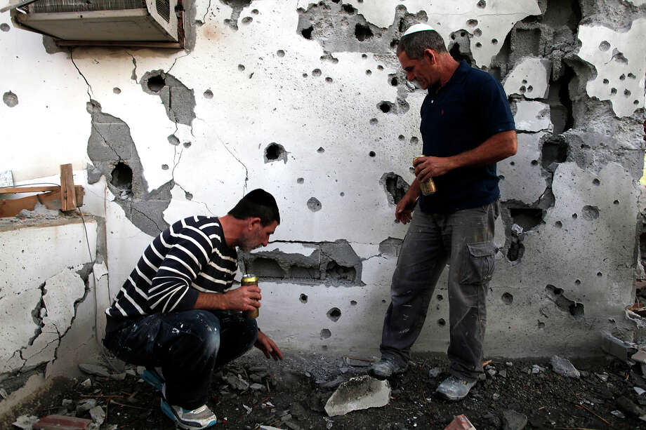 Israelis  inspect the damage to a house that was hit by a rocket fired by Palestinian militants from the Gaza Strip on November 18, 2012 in Ofakim, Israel. Israeli/Gaza attacks have entered the fifth day, with two media buildings being recently struck and several journalists subsequently injured. According to health officials in Gaza, at least 50 Palestinians have been killed since Israel launched operation Pillar of Defense. So far three Israelis have died in the exchange of missiles which followed an air strike on Wednesday that killed Hamas military chief Ahmed Jabari. Photo: Lior Mizrahi, Getty Images / 2012 Getty Images