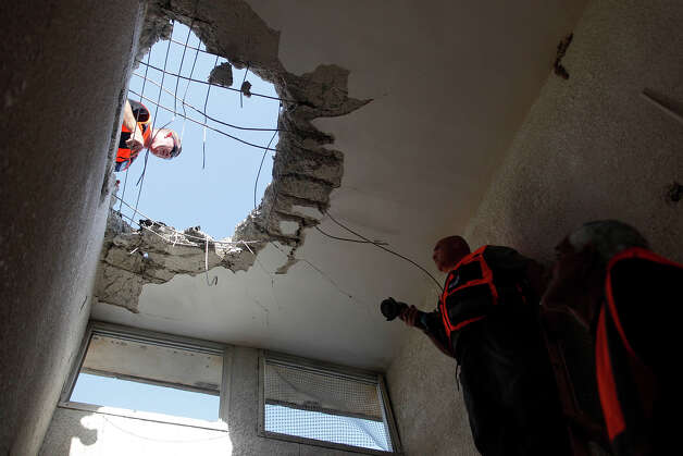 Israeli workers inspect the damage to a house that was hit by a rocket fired by Palestinian militants from the Gaza Strip on November 18, 2012 in Ashkelon, Israel.  Israeli/Gaza attacks have entered the fifth day, with two media buildings being recently struck and several journalists subsequently injured. According to health officials in Gaza, at least 50 Palestinians have been killed since Israel launched operation Pillar of Defense. So far three Israelis have died in the exchange of missiles which followed an air strike on Wednesday that killed Hamas military chief Ahmed Jabari. Photo: Lior Mizrahi, Getty Images / 2012 Getty Images