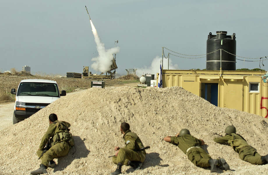 Israeli soldiers take cover as an Israeli missile is launched from the Iron Dome defense missile system, designed to intercept and destroy incoming short-range rockets and artillery shells, in the southern Israeli city of Ashdod in response to a rocket launched from the nearby Palestinian Gaza Strip on November 18, 2012. Sirens sounded across Tel Aviv for a fourth straight day, AFP correspondents said, as Israeli police confirmed two rockets had been intercepted over the city by the Iron Dome defense system. Photo: JACK GUEZ, AFP/Getty Images / 2012 AFP