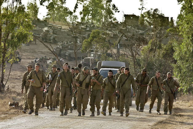 "Israeli soldiers walk at an Israeli army deployment near the Israel-Gaza Strip border on November 18, 2012. Israeli Prime Minister Benjamin Netanyahu said that Israel is ready to ""significantly expand"" its operation against militants in the Hamas-run Gaza Strip as it entered its fifth day. Photo: JACK GUEZ, AFP/Getty Images / 2012 AFP"