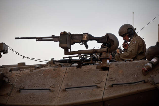 An Israeli soldier sits in his tank in a deployment area on November 19, 2012 on Israel's border with the Gaza Strip. The death toll has risen to at least 85 killed in the air strikes, according to hospital officials, on day six since the launch of operation 'Pillar of Defense.' Photo: Uriel Sinai, Getty Images / 2012 Getty Images