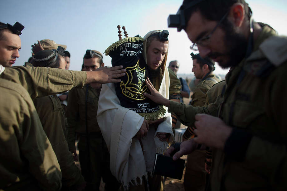 Israeli soldiers perform their morning prayers in a deployment area on November 19, 2012 on Israel's border with the Gaza Strip. The death toll has risen to at least 85 killed in the air strikes, according to hospital officials, on day six since the launch of operation 'Pillar of Defense.' Photo: Uriel Sinai, Getty Images / 2012 Getty Images