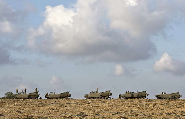 "Israeli soldiers stand by their tanks at an Israeli army deployment area near the Israel-Gaza Strip border on November 18, 2012. Israeli Prime Minister Benjamin Netanyahu said that Israel is ready to ""significantly expand"" its operation against militants in the Hamas-run Gaza Strip as it entered its fifth day. Photo: JACK GUEZ, AFP/Getty Images / 2012 AFP"