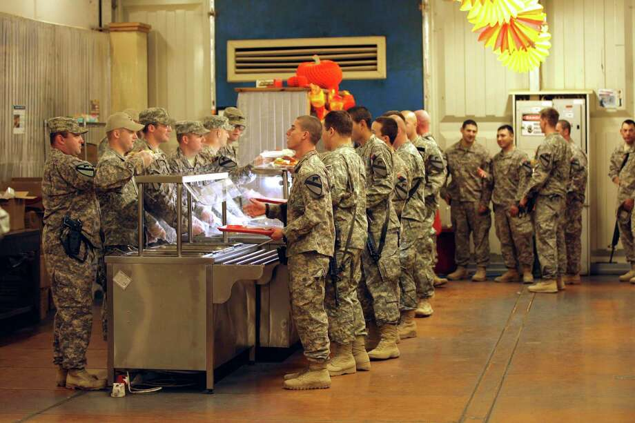 Soldiers line up for a Thanksgiving meal near Baghdad on Nov. 24, 2011. Military dining facilities at home and abroad exude creativity and great food to make Thanksgiving special. Photo: File Photo, Associated Press / AP