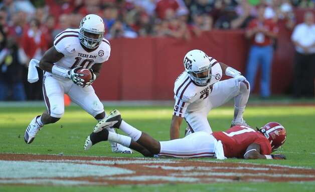 Texas A&M linebacker Sean Porter (10) grabs the interception on a pass intended for Alabama wide receiver Kenny Bell (7) during the first quarter of a college football game at Bryant-Denny Stadium, Saturday, Nov. 10, 2012, in Tuscaloosa.  ( Karen Warren / Houston Chronicle ) (Houston Chronicle)