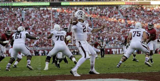 Texas A&M quarterback Johnny Manziel (2) throws from the endzone as the Alabama defense pursues during the first half of an NCAA college football game at Bryant-Denny Stadium in Tuscaloosa, Ala., Saturday, Nov. 10, 2012. (AP Photo/Dave Martin) (Associated Press)