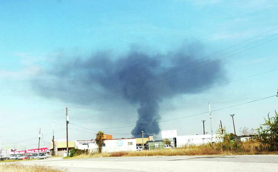 A large plume of smoke is seen from the salvage yard fire. Photo: Johnny Hanson/Chronicle