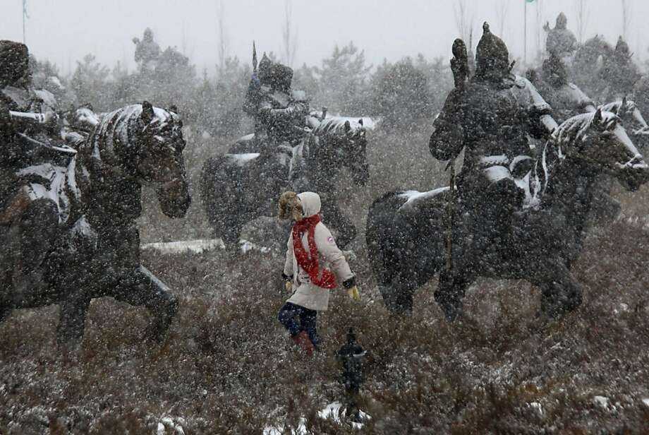 Khan artistry: A tourist visits the horseback warrior sculptures of the Mausoleum of Genghis Khan as the snow falls in Ejin Horo Banner, Inner Mongolia. Photo: Associated Press