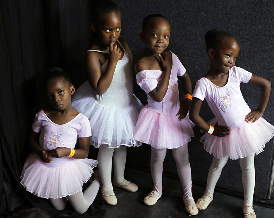 Tiny dancers: Budding ballerinas pose before dancing on stage in Johannesburg. They are part of a South African Mzansi Ballet program that teaches some of the city's poorest children to dance, free of charge. Photo: Denis Farrell, Associated Press
