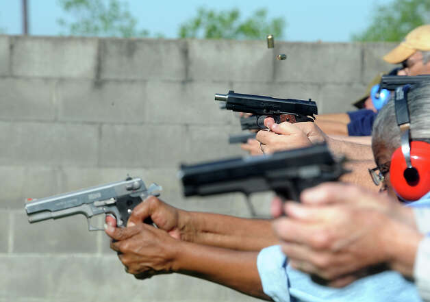 Bullet shells fly out of the guns as students practice at the range during a concealed gun safety class at Leger's Gun Shop and Range in Beaumont, Saturday, March 24, 2012. Tammy McKinley/The Enterprise Photo: TAMMY MCKINLEY