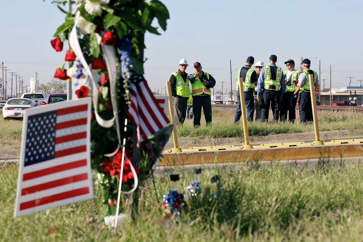 Workers inspect the intersection, Monday Nov. 19, 2012, in Midland, Tx., where a Union Pacific train struck a float carrying military veterans on Thursday Nov. 15, 2012, killing four men, including one from the San Antonio area.