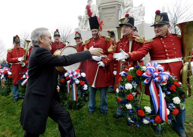 "Director Steven Spielberg, left, greets members of ""The President's Own Band,"" a musical group of Civil War re-enactors, during a ceremony to mark the 149th anniversary of President Abraham Lincoln's delivery of the Gettysburg Address at Soldier's National Cemetery in Gettysburg, Pa., Monday, Nov. 19, 2012. Spielberg and historian Doris Kearns Goodwin were also on hand to deliver remarks and participate in a wreath-laying ceremony. (AP Photo/Patrick Semansky) Photo: Patrick Semansky"