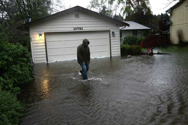 Dan Zarelli walks through a friend's flooded yard near Nathan Hale High School during a significant rainfall on Monday, November 19, 2012. Water running toward Thornton Creek surrounded some homes in the neighborhood. Photo: JOSHUA TRUJILLO / SEATTLEPI.COM