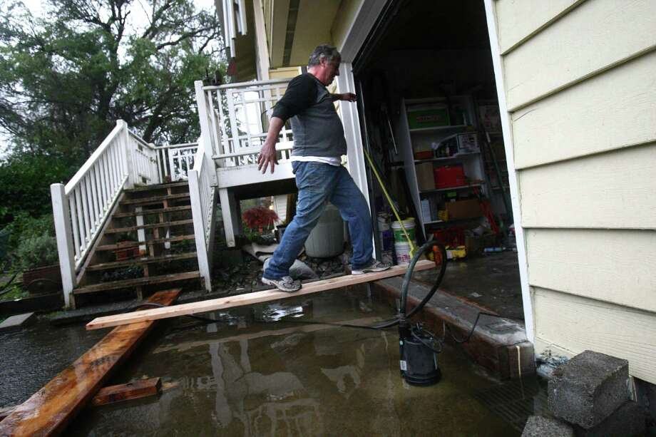 Larry Casey walks across a makeshift bridge into his garage as he works to pump out water from his flooded yard near Nathan Hale High School during a significant rainfall on Monday, November 19, 2012. Water running toward Thornton Creek surrounded some homes in the neighborhood. Photo: JOSHUA TRUJILLO / SEATTLEPI.COM