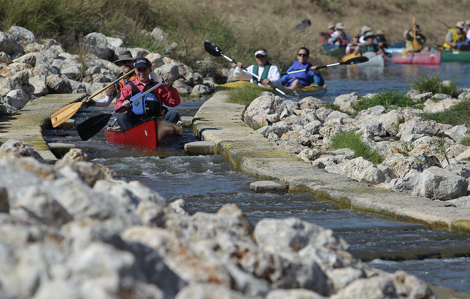Bexar County Judge Nelson Wolff (foreground) heads downstream on a chute on the newly opened Mission Reach Paddling Trail along the San Antonio River near Mission County Park. Kin Man Hui/ Express-News Photo: Kin Man Hui, San Antonio Express-News / ©2012 San Antonio Express-News
