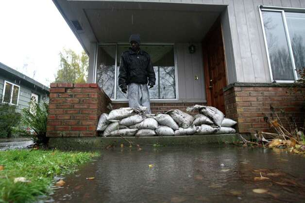 Paul Kiamba watches as water recedes after Seattle Public Utilities successfully cleared a storm drain in front of his house during a significant rainfall on Monday, November 19, 2012. Before the drain near Meadowbrook Pond was cleared the water was inches from spilling over the sandbags into his home. Photo: JOSHUA TRUJILLO / SEATTLEPI.COM