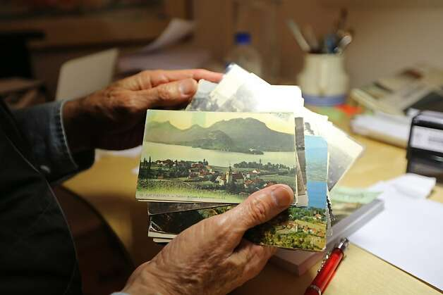 Steve Barrager, 71, shows some of his collection of historic postcards depicting the village of Talloires, France located on Lake Annecy. He collects many of his postcards through flea markets in France, and plans on publishing a book about the village. Steve Barrager has multiple myeloma and has been on a trail drug, Kyprolis, for two and half years which he considers to be a miracle. Photo: Rashad Sisemore, The Chronicle