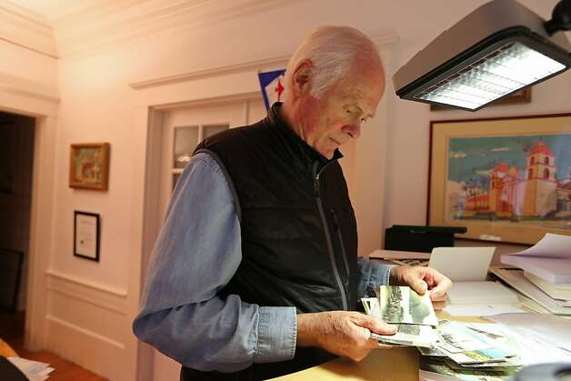 Steve Barrager, 71, looks at his collection of historic postcards depicting the village of Talloires, France located on Lake Annecy. He collects many of his postcards through flea markets in France, and plans on publishing a book about the village. Steve Barrager has multiple myeloma and has been on a trail drug, Kyprolis, for two and half years which he considers to be a miracle. Photo: Rashad Sisemore, The Chronicle