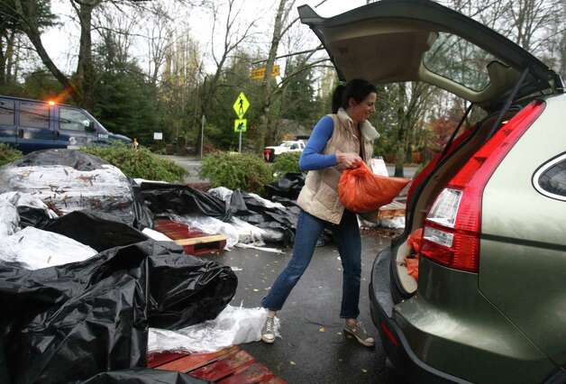 Amy Kaz loads her SUV with sandbags to protect her Bryant neighborhood home during a significant rainfall on Monday, November 19, 2012. Photo: JOSHUA TRUJILLO / SEATTLEPI.COM