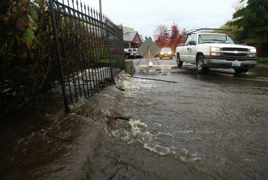 Water flows through the parking lot of Town Centre in Lake Forest Park during a significant rainfall on Monday, November 19, 2012. Photo: JOSHUA TRUJILLO / SEATTLEPI.COM