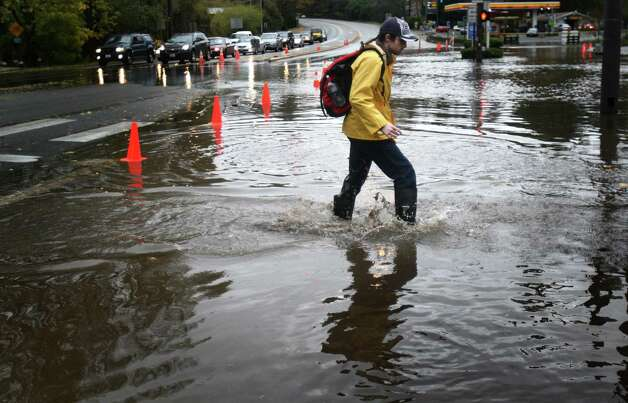 A pedestrian makes his way across a flooded section of Bothell Way NE in Lake Forest Park during a significant rainfall on Monday, November 19, 2012. Photo: JOSHUA TRUJILLO / SEATTLEPI.COM