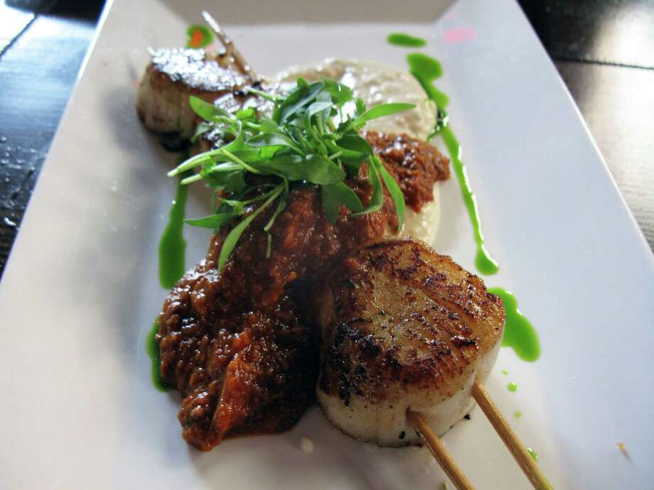 Scallop kebabs  are served with melted Yukons and Romesco sauce.
