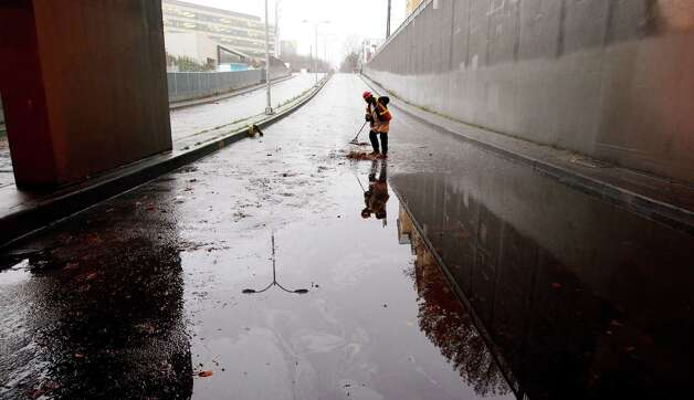 Seattle Public Utility worker Omar Taplin clears out a drain under Highway 99 where the low spot was closed to  traffic after it flooded earlier Monday, Nov. 19, 2012, in Seattle. Wet and windy weather with mountain snow will continue this week in Washington, but there may be a lull  Thanksgiving Day, forecasters said. Photo: Elaine Thompson / Associated Press