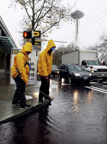 Parking attendants search for a clogged drain as water covers the pedestrian crossing Monday, Nov. 19, 2012, in Seattle. Wet and windy weather with mountain snow will continue this week in Washington, but there may be a lull for turkeys to land on Thanksgiving Day tables, forecasters said. More Pacific storms that started rolling across the Northwest in waves over the weekend are on their way, according to the National Weather Service. Photo: Elaine Thompson / Associated Press
