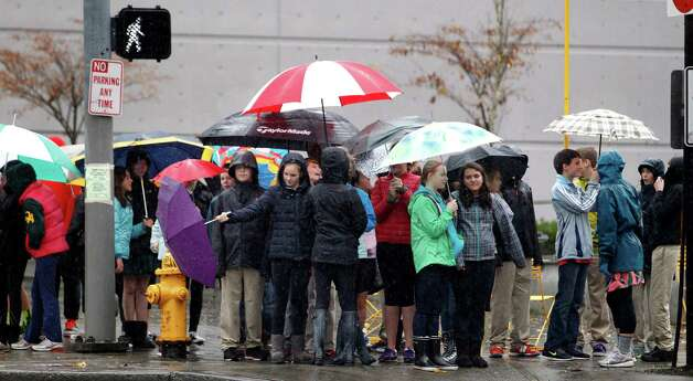 School children huddle under umbrellas as they wait to cross a street during an outing Monday, Nov. 19, 2012, in Seattle. Wet and windy weather with mountain snow will continue this week in Washington, but there may be a lull for turkeys to land on Thanksgiving Day tables, forecasters said. More Pacific storms that started rolling across the Northwest in waves over the weekend are on their way, according to the National Weather Service. Photo: Elaine Thompson / Associated Press