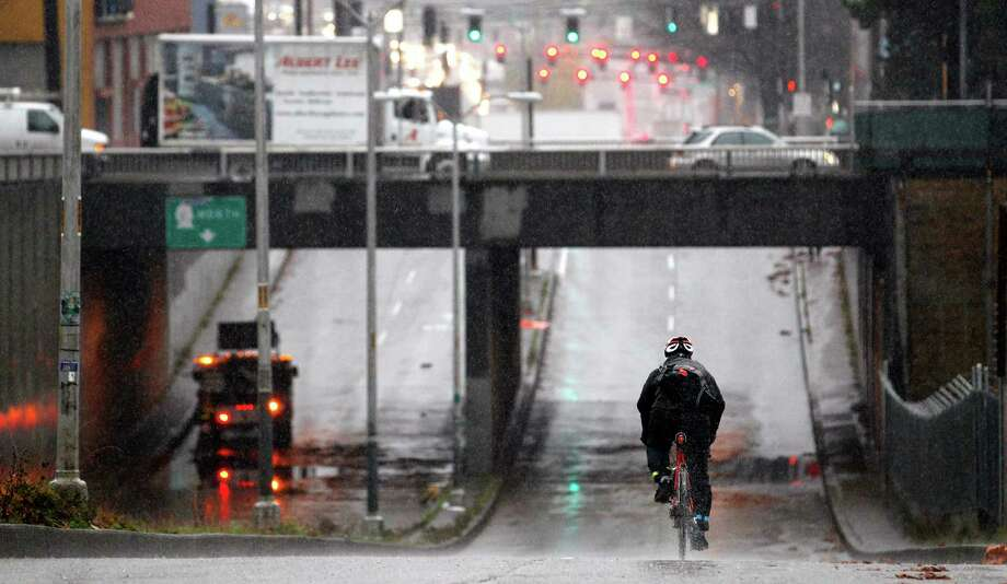 A cyclist has the roadway to himself as he crosses under Highway 99 where the low spot was closed to automotive traffic after it flooded earlier Monday, Nov. 19, 2012, in Seattle. Wet and windy weather with mountain snow will continue this week in Washington, but there may be a lull for turkeys to land on Thanksgiving Day tables, forecasters said. More Pacific storms that started rolling across the Northwest in waves over the weekend are on their way, according to the National Weather Service. Photo: Elaine Thompson / Associated Press
