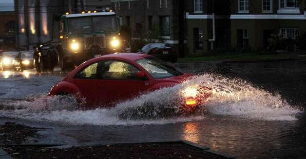 Cars and trucks navigate through standing water, Monday, Nov. 19, 2012, at an intersection in Tacoma, Wash. Wet and windy weather with mountain snow will continue this week in Washington, forecasters said. Photo: Ted S. Warren / Associated Press