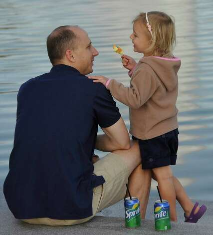 Jonathan McCabe, left, enjoys lunch with his daughter Reese, 4, who wanted to share a frozen treat. The McCabe family had just arrived from South Africa for Thanksgiving. Monday November 19, 2012 was the first of three scheduled Lunch at the Lake events at the new downtown Event Centre. The City of Beaumont provided the music, seating, and scenery, and visitors could get lunch from one of these food vendors that were on site like Big Bo's barbecue, Charles Brewer barbecue, Rao's pizza and gelato, Terrell's ice cream, Wise Guys Grill burgers and fries, and Zummo's sausage and boudain. Others even ordered in advance from Katharine & Co. for their lunches.  Dave Ryan/The Enterprise Photo: Dave Ryan