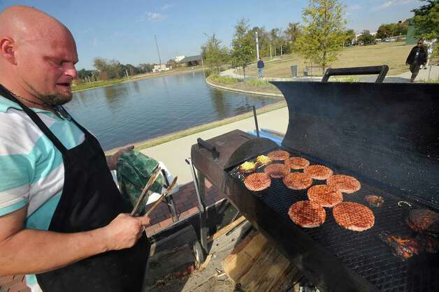 Brent Wise watches over another batch of on-the-spot-grilled hamburgers for his wife Brandi, who was inside the trailer serving the customers. Monday November 19, 2012 was the first of three scheduled Lunch at the Lake events at the new downtown Event Centre. The City of Beaumont provided the music, seating, and scenery, and visitors could get lunch from one of these food vendors that were on site like Big Bo's barbecue, Charles Brewer barbecue, Rao's pizza and gelato, Terrell's ice cream, Wise Guys Grill burgers and fries, and Zummo's sausage and boudain. Others even ordered in advance from Katharine & Co. for their lunches.  Dave Ryan/The Enterprise Photo: Dave Ryan