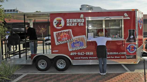 Steve Zummo, left, was busy at the grill of his trailer, as a customer was at the window. Monday November 19, 2012 was the first of three scheduled Lunch at the Lake events at the new downtown Event Centre. The City of Beaumont provided the music, seating, and scenery, and visitors could get lunch from one of these food vendors that were on site like Big Bo's barbecue, Charles Brewer barbecue, Rao's pizza and gelato, Terrell's ice cream, Wise Guys Grill burgers and fries, and Zummo's sausage and boudain. Others even ordered in advance from Katharine & Co. for their lunches.  Dave Ryan/The Enterprise Photo: Dave Ryan