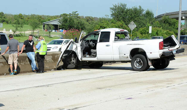 A wrecked truck rests at the divider after an accident on Interstate 10  near Pine Street Monday afternoon. Both lanes were closed due to the accident. Photo taken Monday, July 30, 2012 Guiseppe Barranco/The Enterprise Photo: Guiseppe Barranco, STAFF PHOTOGRAPHER / The Beaumont Enterprise