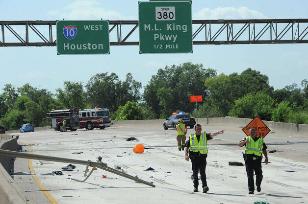 Emergency officials direct west bound traffic off Interstate 10 using an on ramp near Pine Street. An accident on the highway caused both lanes of traffic to be shutdown. Several pieces of debris can be seen in the background.  Photo taken Monday, July 30, 2012 Guiseppe Barranco/The Enterprise Photo: Guiseppe Barranco, STAFF PHOTOGRAPHER / The Beaumont Enterprise