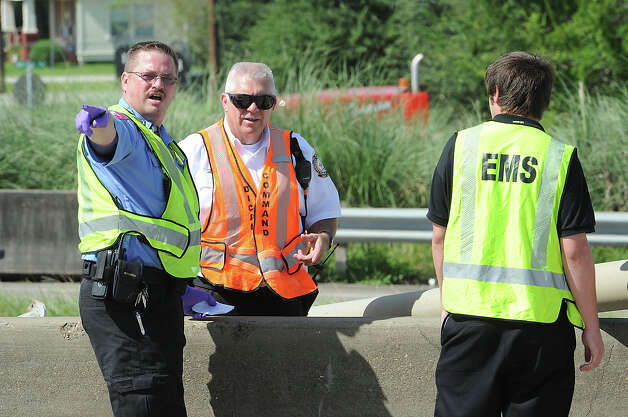 Emergency officials work the scene of an accident that occurred on Interstate 10 near Pine Street on Monday. One person was killed in the wreck and both lanes of traffic were closed. Photo taken Monday, July 30, 2012 Guiseppe Barranco/The Enterprise Photo: Guiseppe Barranco, STAFF PHOTOGRAPHER / The Beaumont Enterprise