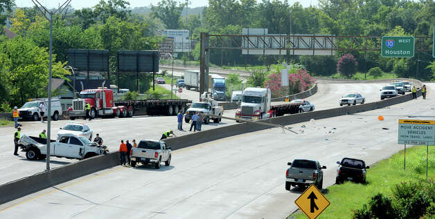 A woman was killed Monday afternoon after an accident occurred on Interstate 10 near Pine Street. Seven separate wrecks on both sides of the highway stemmed from the original accident that began in the east bound lane. Both lanes were shutdown by emergency officials.  Photo taken Monday, July 30, 2012 Guiseppe Barranco/The Enterprise Photo: Guiseppe Barranco, STAFF PHOTOGRAPHER / The Beaumont Enterprise