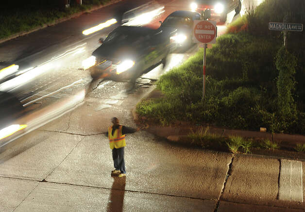 A woman directs traffic on the feeder road of Interstate 10 and Magnolia Avenue Monday night due to a fatal accident that occurred earlier in the day. Photo taken Monday, July 30, 2012 Guiseppe Barranco/The Enterprise Photo: Guiseppe Barranco, STAFF PHOTOGRAPHER / The Beaumont Enterprise