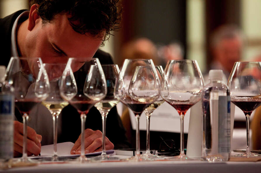 Professional wine tasters make notations about different wines during the Top Taster Blind Wine Tast