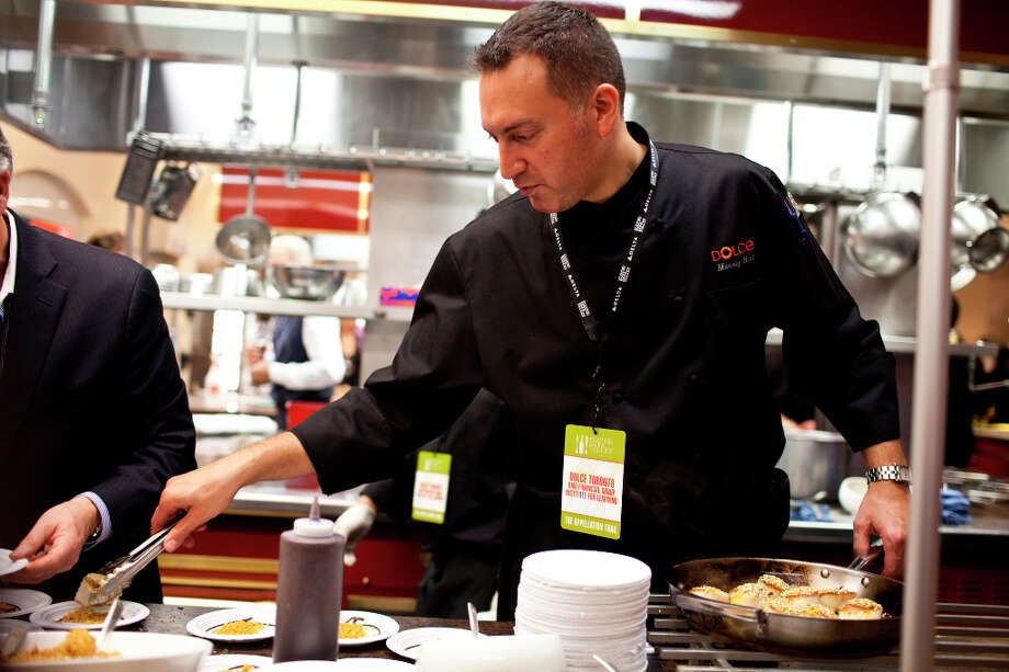 Chef Murray Hall, of Dolce Toronto, right, makes day boat seared scallop with applewood smoked macron almonds, cilantro cream, icicle radish slaw, toasted hemp seeds, and dried Meyer lemons. Photo: Jason Henry, Special To The Chronicle / ONLINE_YES