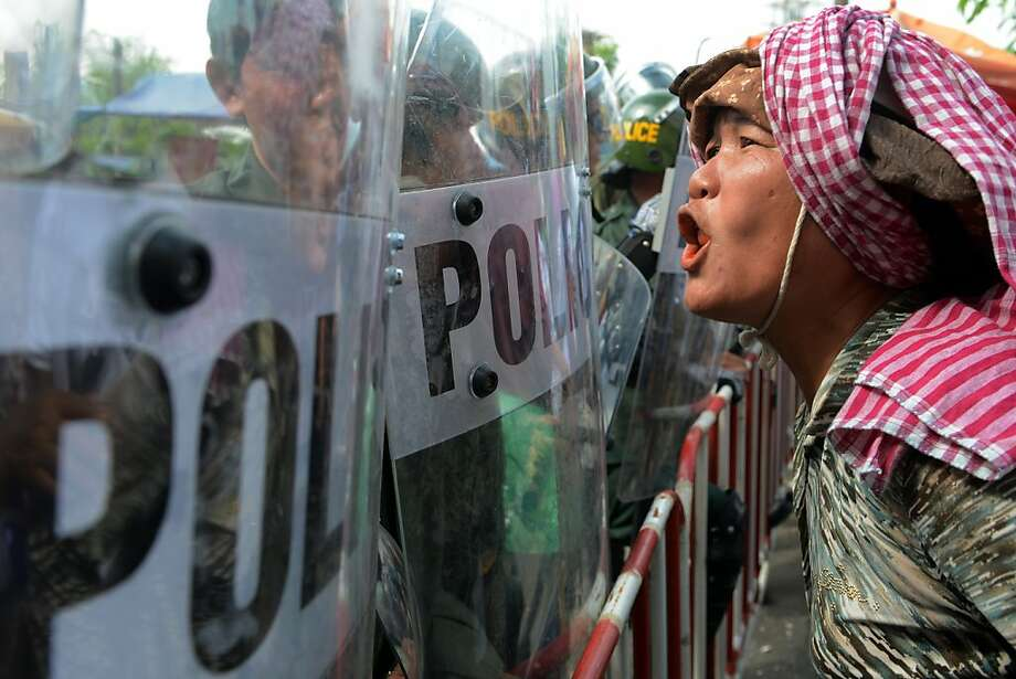 A protester in Cambodia confronts police in Phnom Penh, where the Association of Southeast Asian Nations is meeting and President Obama is making the first visit of a U.S. chief executive. Photo: Tang Chhin Sothy, AFP/Getty Images