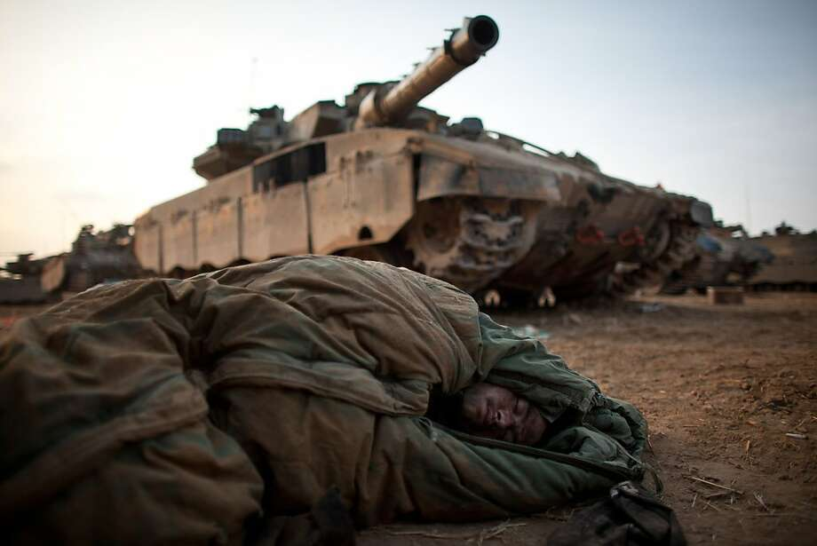 An Israeli soldier sleeps next to tanks near the border with the Gaza Strip. At least 111 Palestinians have been killed in Israeli air strikes, and Gaza fighters are firing dozens of missiles a day into Israel. Photo: Uriel Sinai, Getty Images