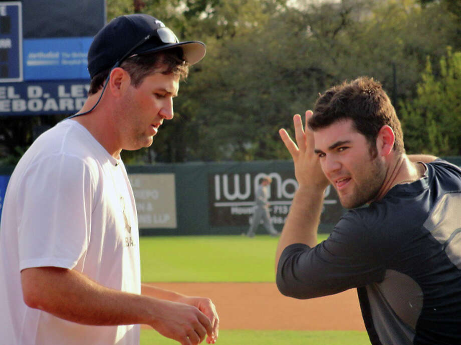 Volunteer assistant coach Lance Berkman offers tips to Michael Aquino. (Joseph Duarte / Chronicle)
