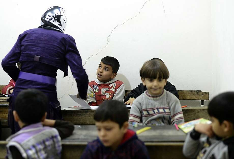 Syrian children interact with their teacher in a classroom at their new school in the Tarik al-Bab neighborhood of Aleppo on November 18, 2012. Of some 22,000 schools across Syria, more than 2,000 have been damaged or destroyed and over 800 have been turned into makeshift shelters for refugee families, according to UNICEF. AFP PHOTO/ FRANCISCO LEONGFRANCISCO LEONG/AFP/Getty Images Photo: Francisco Leong, AFP/Getty Images