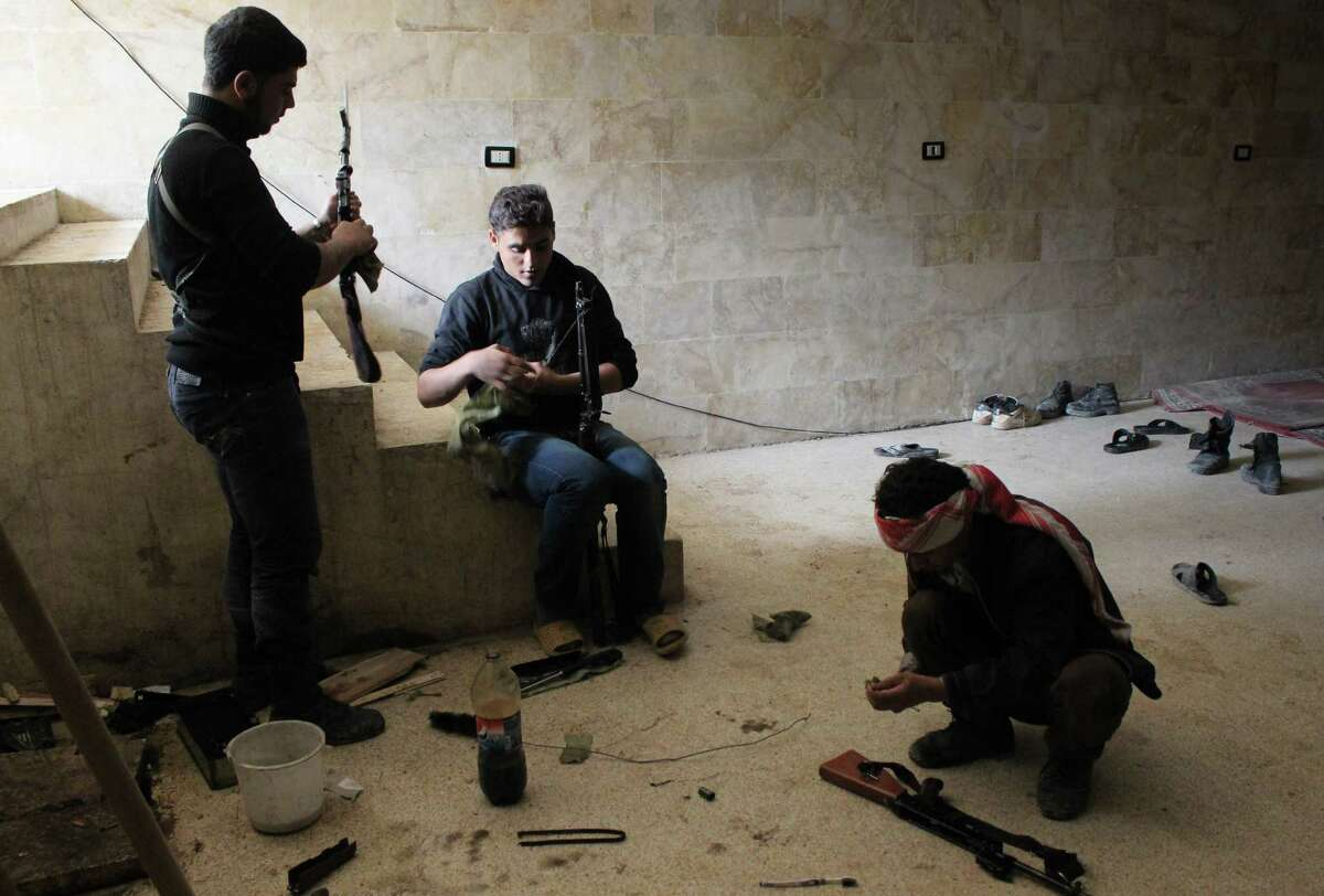 In this Saturday, Nov. 17, 2012 photo, rebels of the Free Syrian Army clean their weapons as airstrikes by the Syrian air force drive the rebels underground, in the northwestern city of Maraat al-Numan, Syria. After months of fierce fighting for control of the vital Aleppo-Damascus highway, the rebels have succeeded in pushing the Syrian army out of the center of Maraat al-Numan located on the highway between Aleppo and Hama. (AP Photo/Mustafa Karali)