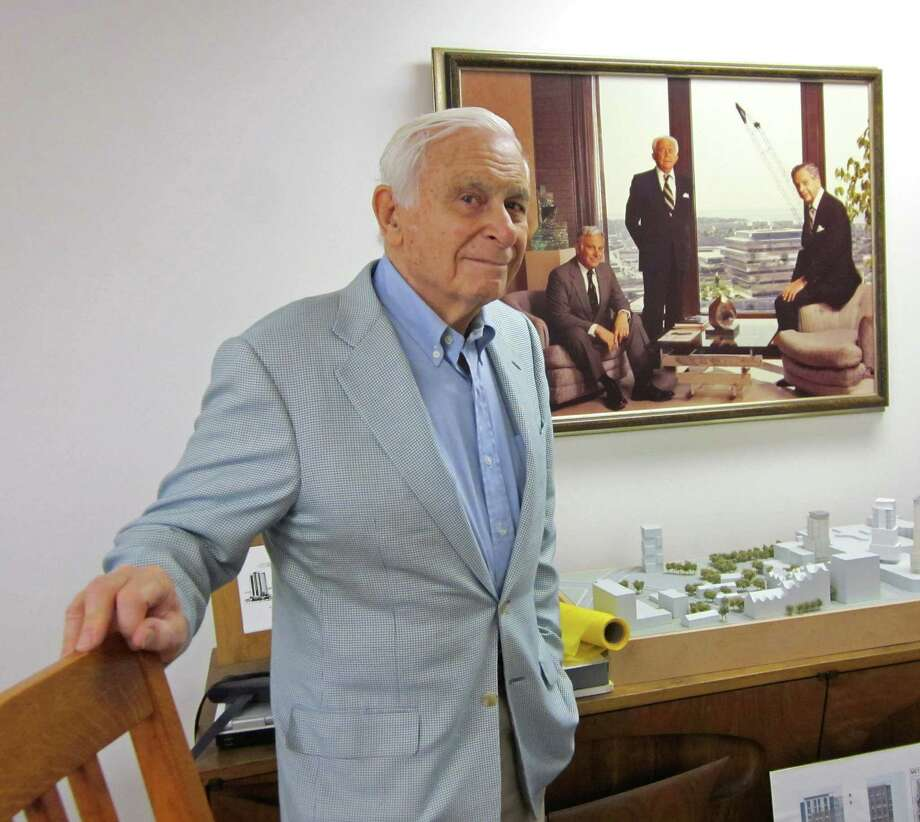 Robert N. Rich in his office on Summer Street in downtown Stamford in August 2012. Behind Rich is an image of him, on the left, with his father, F.D. Rich Sr., center, and brother F.D. Rich Jr. Robert N. Rich died Saturday, Nov. 17, 2012 at his Shippan Point home in Stamford at age 84 after a brief battle with leukemia. Photo: Contributed Photo