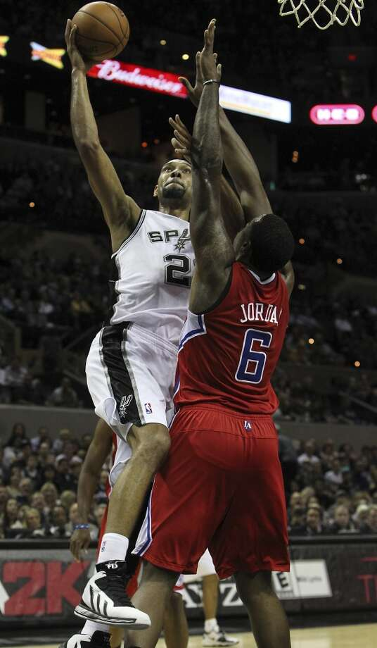 Spurs' Tim Duncan (21) drives to the basket against Los Angeles Clippers' DeAndre Jordan (06) in the first half of their game at the AT&T Center on Monday, Nov. 19, 2012. (Kin Man Hui / San Antonio Express-News)